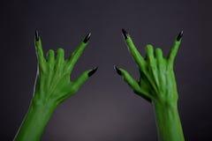 Grüne Monsterhände mit den schwarzen Nägeln, die Schwermetallgeste zeigen Stockfotos