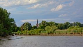 Grüne natürliche Grenzen von Fluss Schelde mit kleiner Kirche, Flandern, Belgien Lizenzfreie Stockbilder