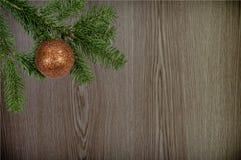 Grüne Niederlassung mit Weihnachtsball auf hölzernem Hintergrund Lizenzfreies Stockbild