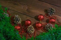 Grüne Niederlassungen reichlich verziert mit Spielwaren, um die Weihnachtsbaum- und Kiefernkegel auf einem Holztisch zu verzieren stockbilder