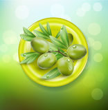 grüne Oliven auf einer grünen Platte stock abbildung