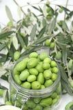 Grüne Oliven in einem Glasglas Stockfoto