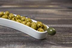 Grüne Oliven im Vase auf Holztisch Lizenzfreie Stockfotografie