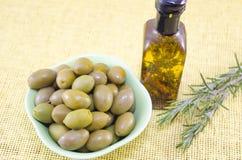 Grüne Oliven und eine Flasche reines Olivenöl Stockfotos