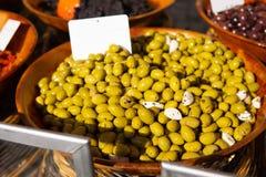Grüne Oliven und in Essig eingelegter Knoblauch am Landwirtmarkt für Verkauf stockfotografie