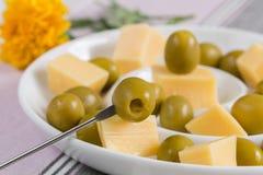 Grüne Oliven und Käseaperitif in einem weißen Teller Lizenzfreies Stockbild