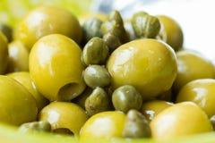 Grüne Oliven und Kapriolen in der Schüssel, Nahaufnahme, italienische Bestandteile Stockbilder