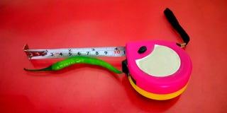 Grüne Paprikamaße mit Meterband lizenzfreies stockbild