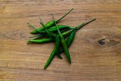 Grüne Paprikas auf hölzernem Lizenzfreies Stockfoto