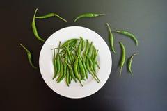 Grüne Paprikas an in der weißen Platte auf dunklem Tabellenhintergrund Lizenzfreies Stockfoto