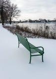 Grüne Parkbank im Schnee Stockfoto