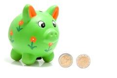 Grüne piggy Querneigung mit Münzen Stockbild