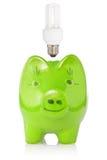 Grüne Piggyquerneigung mit Glühlampe Stockfotografie