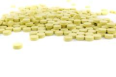 grüne Pillen auf weißem Boden Stockfotos