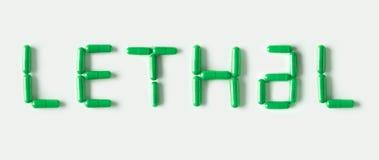 Grüne Pillenkapseln in Form des Wortes tödlich Lebenkonzept lokalisiert Lizenzfreies Stockfoto