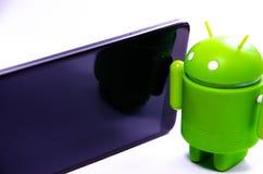 Gr?ne Plastik-Android-Zahl auf einem wei?en Hintergrund und mit einem Smartphone lizenzfreie stockfotos