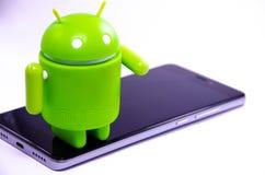 Gr?ne Plastik-Android-Zahl auf einem wei?en Hintergrund und mit einem Smartphone stockfotos