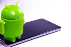Gr?ne Plastik-Android-Zahl auf einem wei?en Hintergrund und mit einem Smartphone stockbilder
