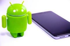 Gr?ne Plastik-Android-Zahl auf einem wei?en Hintergrund und mit einem Smartphone stockbild