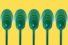 Grüne Plastiklöffel in einer abstrakten Zusammensetzung stockbilder