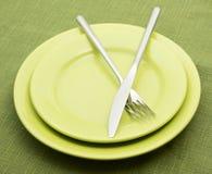 Grüne Platten mit Gabel und Messer Stockfotos