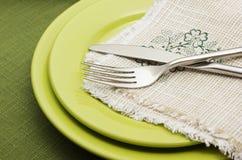 Grüne Platten mit Gabel und Messer Lizenzfreie Stockfotos