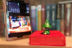 Grüne Puppen-aufpassendes Tablet im Buch-Kabinett Lizenzfreie Stockfotos