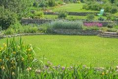 Grüne Rasen und Blumenbeete im Garten Stockbild