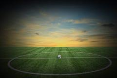 Grüne Rasenfläche des Fußballs bei Sonnenuntergang Lizenzfreie Stockfotografie