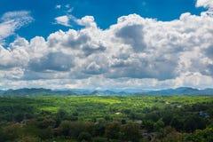 Grüne Rasenfläche-Wiese mit Holz und Berg unter blauem Himmel Lizenzfreies Stockfoto