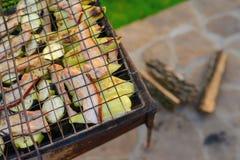 Grüne reife Zucchini mit den Scheiben des saftigen Speckes braten auf einem Grill über einem Feuer lizenzfreie stockfotografie