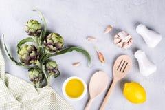 Grüne rohe Artischockenköpfe kochfertig Artischocken und Bestandteile Knoblauch, Zitrone und Olivenöl Stockbild