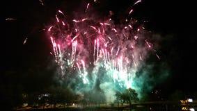 Grüne/rote Feuerwerke durch den Fluss Lizenzfreie Stockfotos