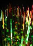 Grüne, rote Lichter und Strahlen auf dem schwarzen Hintergrund, strukturierter Beleuchtungshintergrund, digitales Fasergras, Taut Stockbild