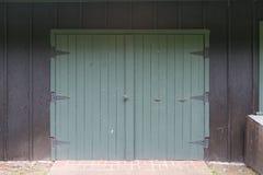Grüne Scheunen-Türen auf schwarzer Wand Stockfotos