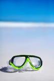 Grüne Schnorchel und wasserdichte Maske, die auf Sand hinter blauem Himmel liegt Stockbild