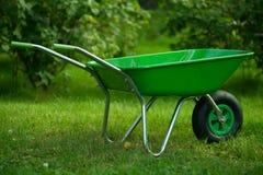 Grüne Schubkarre im grünen Garten Stockfotografie