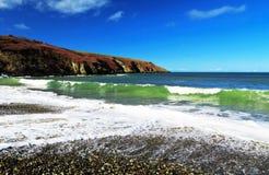 Grüne Smaragdwellen, die auf ein Pebble Beach zusammenstoßen Stockbild