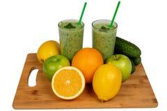 Grüne Smoothies und Früchte auf Küche verschalen auf weißem Hintergrund lizenzfreie stockfotos