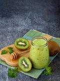 Grüne Smoothies von der Kiwi, vom Hafermehl, von den Nüssen und vom Honig auf dunklem Hintergrund Lizenzfreies Stockbild