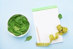 Grüne Spinatsblätter, -notizbuch und -Maßband auf blauer Tischplatteansicht Diät und gesundes Lebensmittelkonzept stockbild