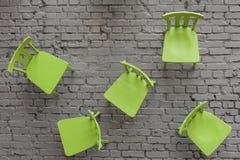 Grüne Stühle, örtlich festgelegt auf einer grauen Backsteinmauer Stockbilder