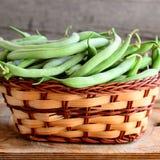 Grüne Stangenbohnen in einem Weidenkorb und in einem hölzernen Brett Rohe junge Bohnenhülsen Alter hölzerner Hintergrund Saisoner Lizenzfreie Stockfotos