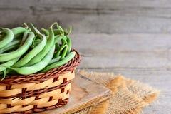 Grüne Stangenbohnen in einem Weidenkorb und in einer Leinwand Natürliche unausgereifte Bohnenhülsen Rustikaler hölzerner Hintergr Stockfotos