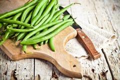 Grüne Stangenbohnen und Messer Stockfotos