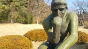 Grüne Statue des Denkers Auguste Rodin, stellend nackt auf einem Felsen ein lizenzfreie stockbilder