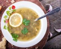 Grüne Suppe in einer Schale mit einem Löffel auf einem hölzernen Brett Lizenzfreies Stockfoto