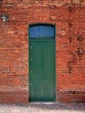 Grüne Tür in der Backsteinmauer Stockfoto
