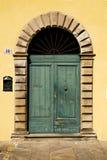 Grüne Tür mit Bogen in einer gelben Wand, Italien Stockfotografie
