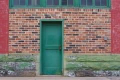 Grüne Tür u. Backsteinmauer Stockfotos